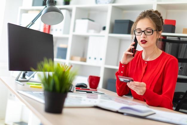 Una niña sentada en el escritorio de la oficina, con una tarjeta bancaria y un teléfono en la mano.