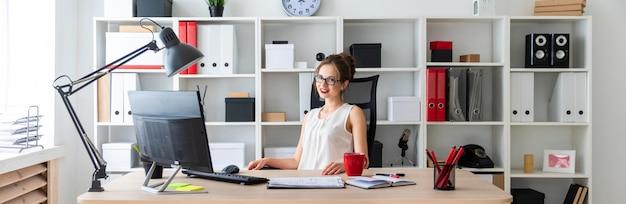 Una niña sentada en el escritorio de la oficina.