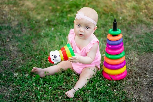 Niña sentada en la hierba en el verano y jugando pirámide