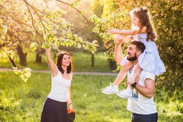 Niña sentada en el hombro de su padre recogiendo la hoja del árbol con la madre