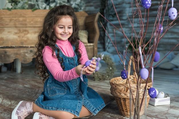 Niña sentada con huevo de pascua cerca de ramas en florero