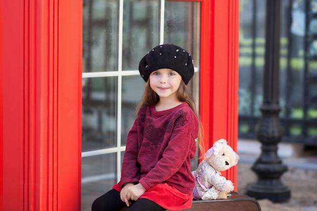 Niña sentada en una maleta con un oso de peluche. cabina telefónica roja de londres. primavera. otoño. con el día internacional de la mujer. ¡desde el 8 de marzo! retrato de primer plano de la cara niña pequeña.