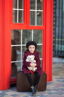 La niña está sentada en una maleta con un oso de peluche. cabina telefónica roja de londres. primavera. otoño. el viaje. londres, inglaterra. primavera. chica de escuela. vacaciones escolares. niña con boina y abrigo