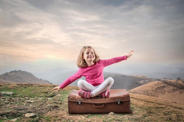 Niña sentada en una maleta de viaje