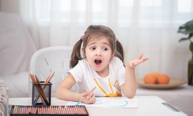 La niña está sentada a la mesa y haciendo los deberes.