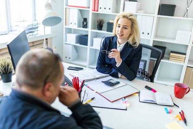 Una niña sentada en una mesa en la oficina, sosteniendo copas en la mano y hablando con un hombre.