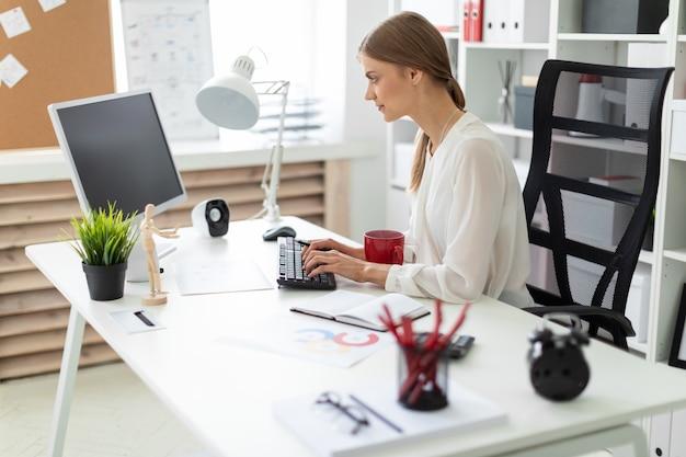 Una niña sentada en una mesa en la oficina, sosteniendo una taza roja en la mano y trabajando en la computadora.
