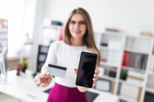 Una niña sentada en una mesa y sosteniendo un teléfono y una tarjeta de crédito.