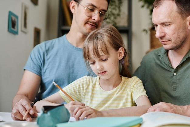 Niña sentada en la mesa y tomando notas en el cuaderno con profesores ayudándola en el estudio