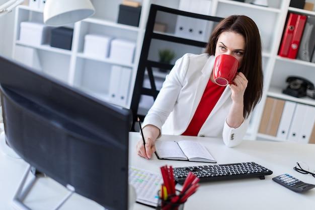 Una niña sentada en la oficina en la computadora escritorio y sosteniendo una taza roja.