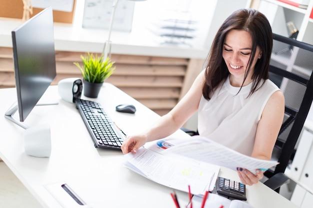 Una niña sentada en la oficina en una computadora escritorio y trabajando con documentos y una calculadora.