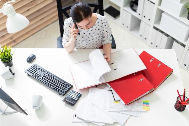 Una niña sentada en la oficina en la computadora escritorio, trabajando con documentos y hablando por teléfono.