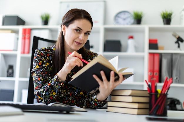 Una niña sentada en la oficina en la computadora escritorio y trabajando con un libro.