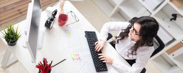 Una niña está sentada en la oficina en la computadora y trabajando con documentos.