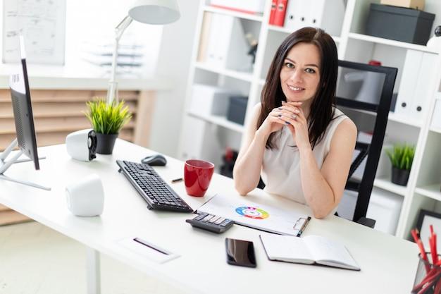 Una niña sentada en la oficina en la mesa de la computadora.