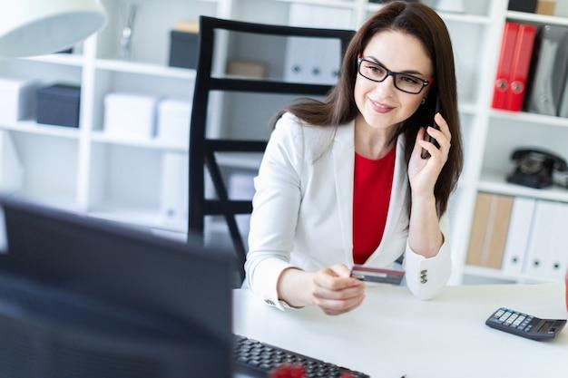 Una niña sentada en la oficina en la mesa y sosteniendo una tarjeta bancaria y teléfono.