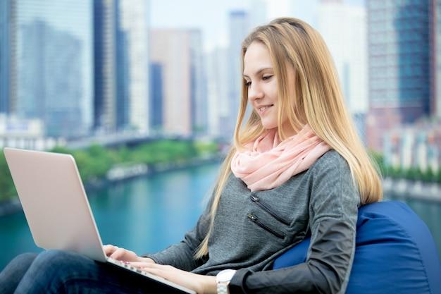 Niña sentada con ordenador portátil, paisaje urbano en el fondo