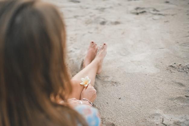 La niña esta sentada en la playa