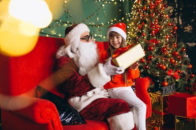 Niña sentada con santa y regalos en navidad