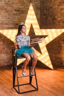Niña sentada en la silla alta ensayando delante de estrella brillante contra la pared de ladrillo