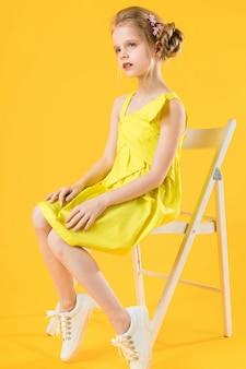 Una niña está sentada en una silla blanca sobre una amarilla.