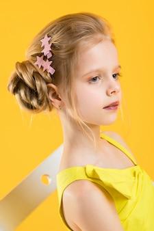 Una niña está sentada en una silla blanca sobre una pared amarilla.