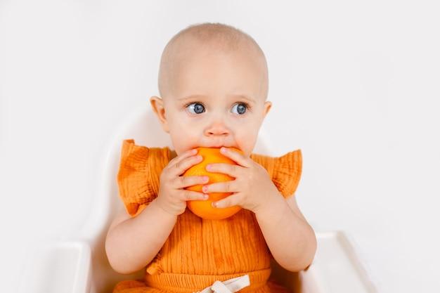 Niña sentada en la silla del niño comiendo frutas en blanco