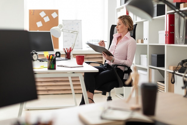 Una niña sentada en una silla en la oficina y sostiene documentos y un lápiz en sus manos.