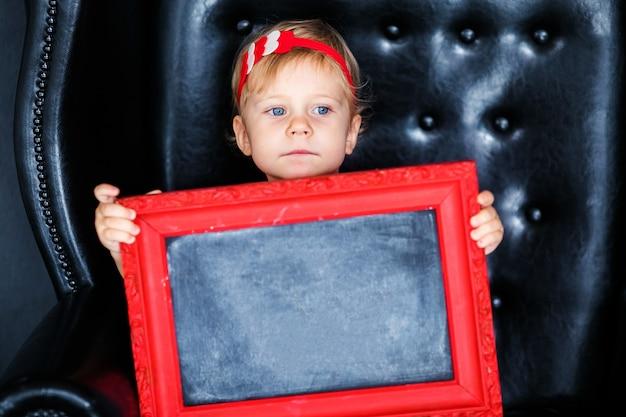 Niña sentada en el sillón con una imagen enmarcada en rojo en el día de san valentín