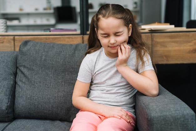 Niña sentada en un sofá gris que sufre de dolor de muelas