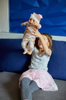 Niña sentada en el sofá de la habitación en casa jugando con la muñeca, cantando canciones, como mamá.