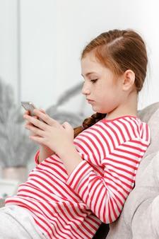 Niña sentada en el sofá juega teléfono inteligente en la sala de estar