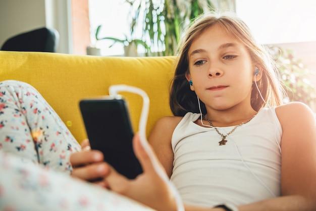Niña sentada en el sofá y usando teléfonos inteligentes