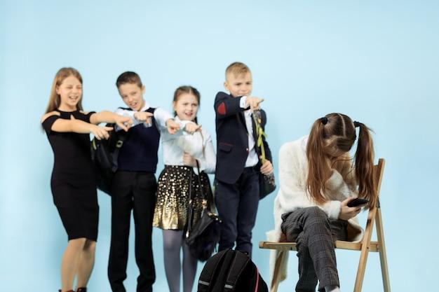 Niña sentada sola en una silla y sufriendo un acto de acoso mientras los niños se burlan. triste colegiala joven sentada contra la pared azul.