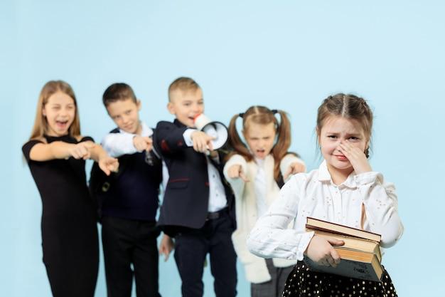 Niña sentada sola en una silla y sufriendo un acto de acoso mientras los niños se burlan. triste colegiala joven sentada sobre fondo azul.