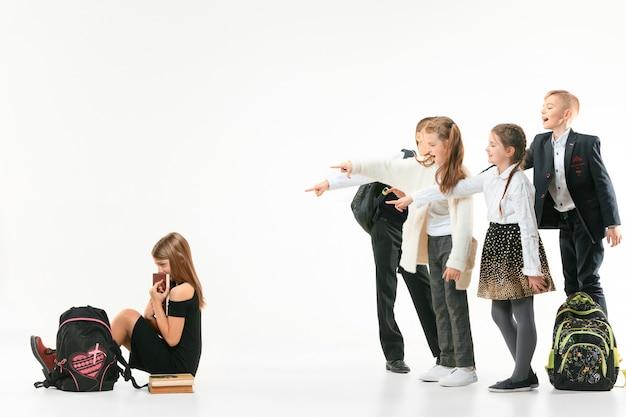 Niña sentada sola en el suelo y sufriendo un acto de intimidación mientras los niños se burlan