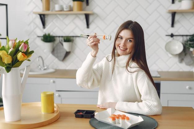 Niña sentada en su casa en la mesa con un sushi