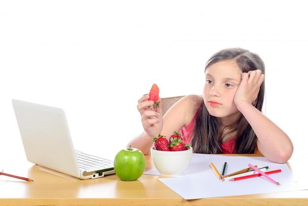 Una niña sentada en su escritorio comiendo una fresa
