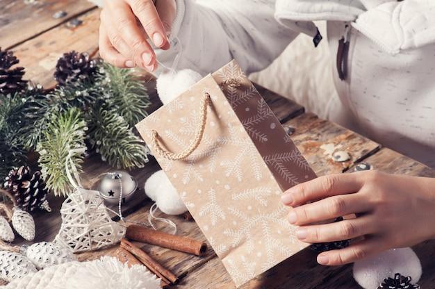 Niña sentada en su escritorio embalaje regalo de navidad