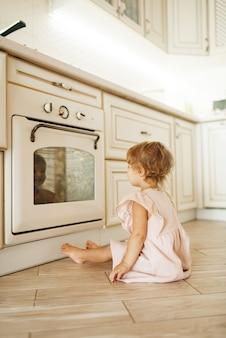 Niña sentada en el suelo en el horno de cocción y mirando el proceso de preparación de los pasteles.