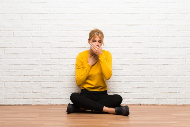 La niña sentada en el suelo sufre de tos y se siente mal
