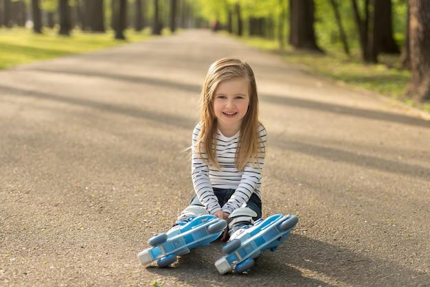 Niña sentada en la tierra, descansando del patinaje