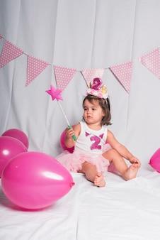 Una niña sentada con una varita y globos de color rosa sobre blanco.