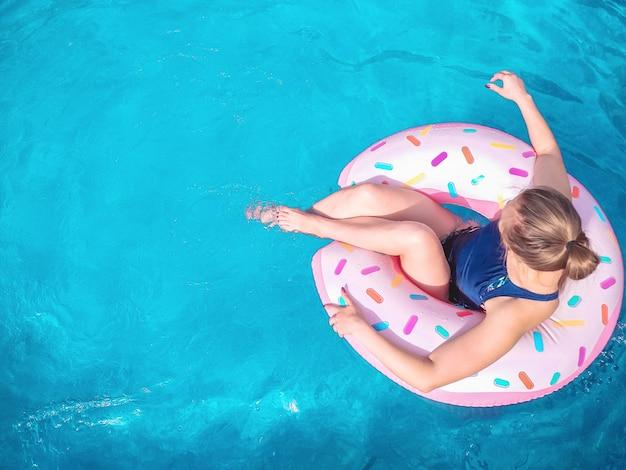La niña se sienta en un anillo de goma en forma de rosquilla en una piscina azul. tiempo para relajarse en un colchón de aire. copie el espacio.