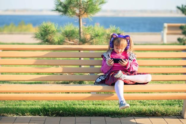 Una niña se sienta en un banco en el parque y mira las caricaturas del teléfono a través de auriculares inalámbricos. el problema de los niños modernos con artilugios.