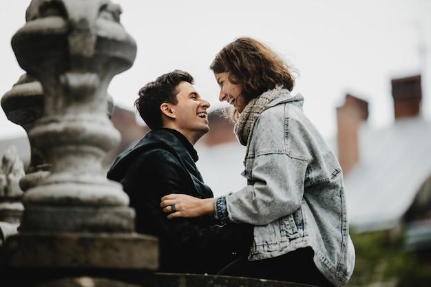 La niña se sienta en la barandilla de un edificio antiguo y le sonríe al tipo parado frente a ella
