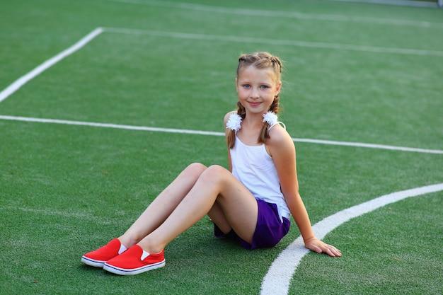 La niña se sienta en el cordel en el campo de deportes.