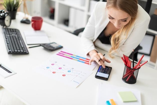 Una niña se sienta en el escritorio de una computadora en la oficina y cuenta con una calculadora en el teléfono.