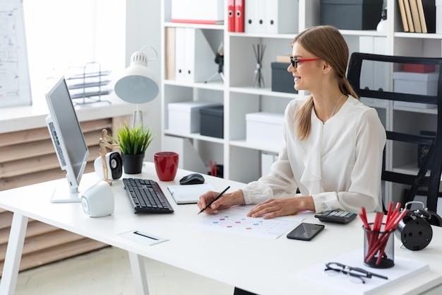Una niña se sienta en el escritorio de una computadora en la oficina y sostiene un lápiz en la mano.
