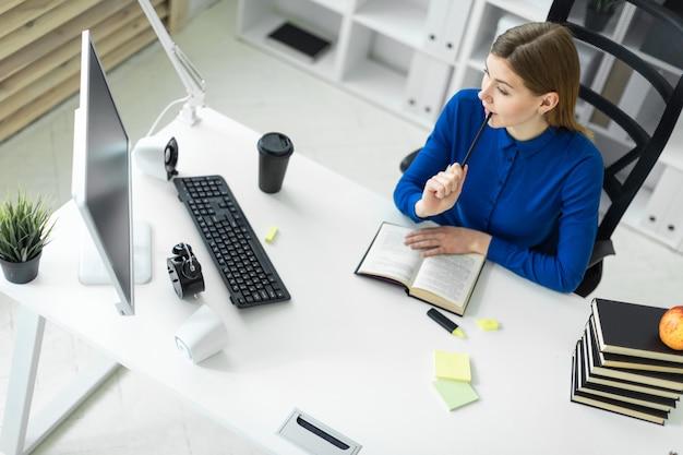 Una niña se sienta en el escritorio de una computadora y sostiene un lápiz en la mano. antes de que la niña mienta un libro abierto.